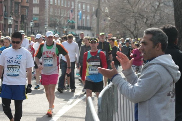 Leonardo Medina applauds as the runners who were unable to finish before the race's supension pass along the marathon route after about an hour of waiting. They were never allowed to finish.