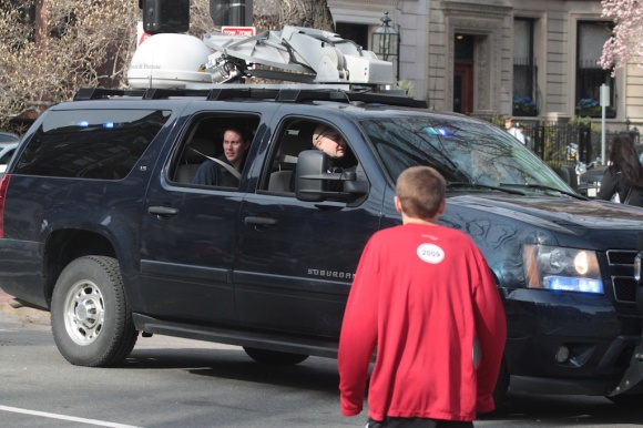 An SUV with U.S. Government plates and a roof-mounted satellite arrives at the scene. It was waved through toward the marathon finish line.